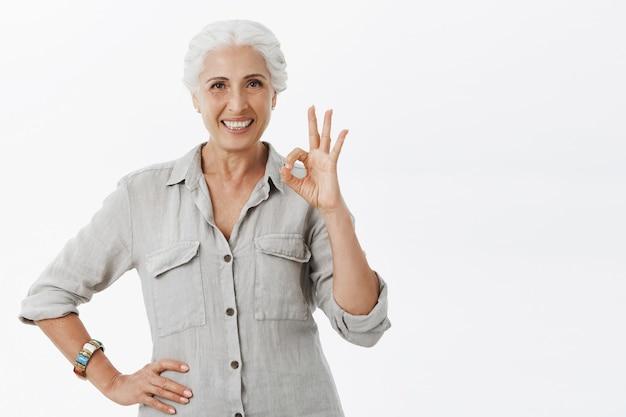 Zadowolona uśmiechnięta starsza pani pokazująca dobry gest na aprobatę, polecam towarzystwo, podoba mi się pomysł