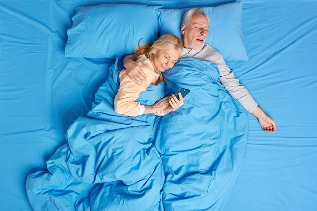 Zadowolona uzależniona od nowoczesnych technologii kobieta korzysta z telefonu komórkowego w łóżku, uściskana przez śpiącego męża, przewija internet przed snem. para rodzin w średnim wieku odpoczywa w przytulnej sypialni.