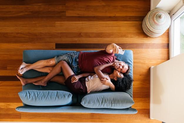 Zadowolona wieloetniczna para bierze selfie na smartphone wpólnie