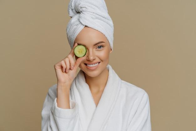 Zadowolona wypoczęta kobieta zakrywa oko plastrem świeżego ogórka, który dba o skórę