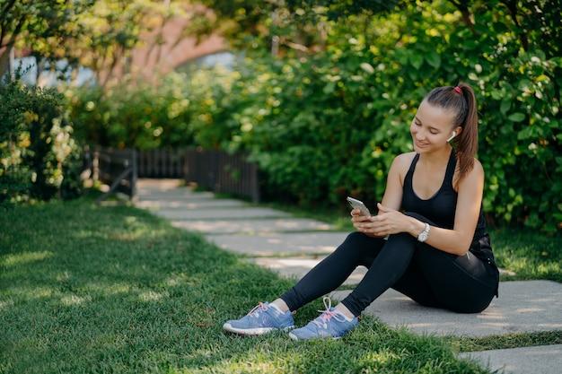 Zadowolona wysportowana kobieta w sportowym stroju uśmiecha się radośnie surfuje po telefonie komórkowym, słuchając muzyki przez bezprzewodowe słuchawki robi sobie przerwę po słonecznym poranku trening korzysta z aplikacji do śledzenia aktywności