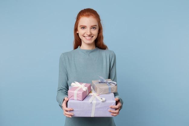 Zadowolona z okazji urodzin kobieta trzyma przed pudełkami z prezentami gratulacje i uśmiecha się