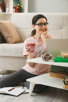 Zadowolona z ręką pod brodą młoda dziewczyna trzyma filiżankę herbaty w okularach, siedząc na podłodze za stolikiem kawowym w salonie