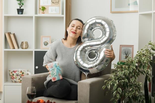 Zadowolona z zamkniętych oczu piękna kobieta w szczęśliwy dzień kobiet trzymająca balon z numerem osiem z prezentem siedzącym na fotelu w salonie