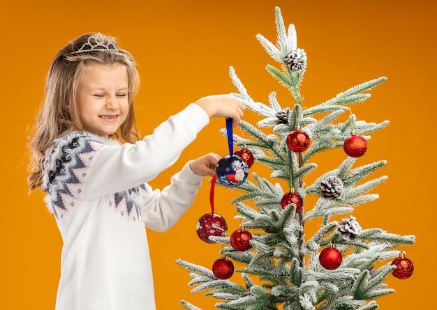 Zadowolona z zamkniętymi oczami dziewczynka stojąca w pobliżu choinki ubrana w tiarę z girlandą na szyi trzymająca bombki odizolowane na pomarańczowym tle