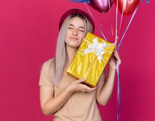 Zadowolona z zamkniętymi oczami młoda piękna dziewczyna w kapeluszu imprezowym trzymająca balony z pudełkiem na prezent