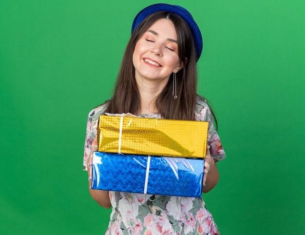 Zadowolona z zamkniętymi oczami młoda piękna dziewczyna w kapeluszu imprezowym trzymająca pudełka na prezenty na zielonej ścianie