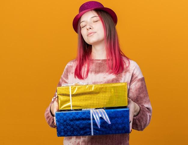 Zadowolona z zamkniętymi oczami młoda piękna dziewczyna w kapeluszu imprezowym trzymająca pudełka na prezenty