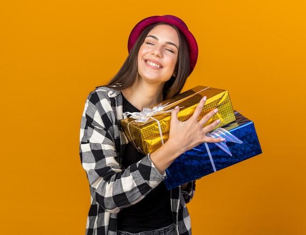 Zadowolona z zamkniętymi oczami młoda piękna kobieta w kapeluszu imprezowym trzymająca pudełka na prezenty na pomarańczowej ścianie