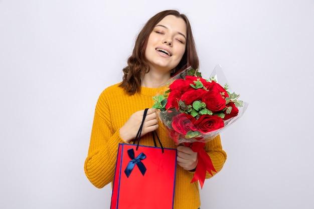 Zadowolona z zamkniętymi oczami piękna młoda dziewczyna na szczęśliwy dzień kobiety trzymająca torbę na prezent z bukietem na białym tle