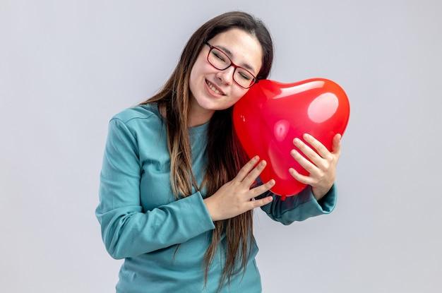 Zadowolona z zamkniętymi oczami, przechylająca głowę młoda dziewczyna na walentynki trzymająca balon w kształcie serca na białym tle