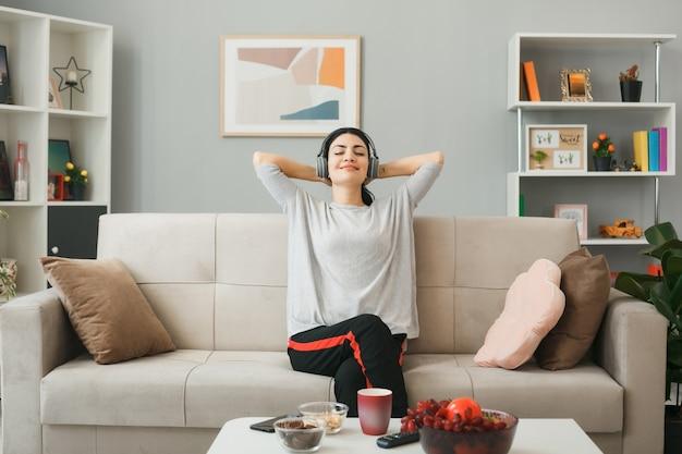 Zadowolona z zamkniętymi oczami z rękami za głową młoda dziewczyna w słuchawkach siedząca na kanapie za stolikiem kawowym w salonie