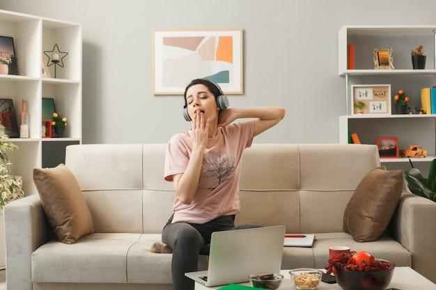Zadowolona z zamkniętymi oczami zasłoniętymi ustami dłonią młoda dziewczyna w słuchawkach siedząca na kanapie za stolikiem kawowym w salonie