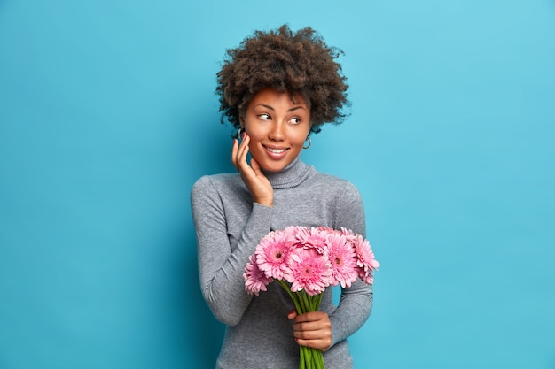 Zadowolona, zachwycona african american kobieta trzyma bukiet różowych gerbery