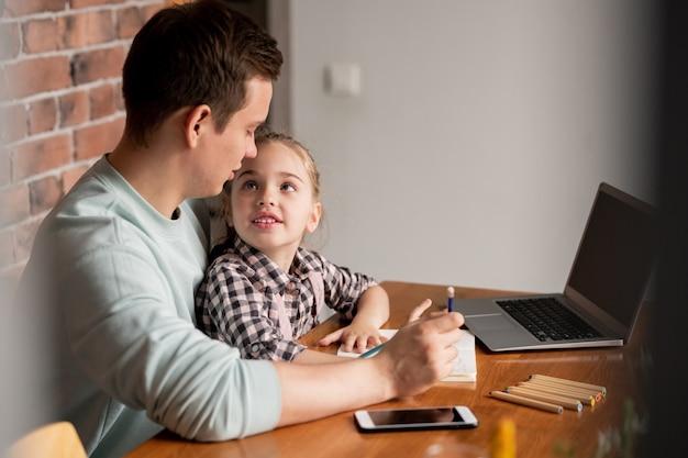 Zadowolona zaciekawiona piękna córka w kraciastej koszuli siedzi przy stole i patrzy na ojca, pytając go o kreatywne pomysły