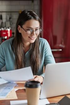 Zadowolona, zadowolona młoda kobieta tworzy udany plan na bankowość, trzyma papierowe dokumenty, pozytywnie patrzy na laptop, siada przy kuchennym stole.