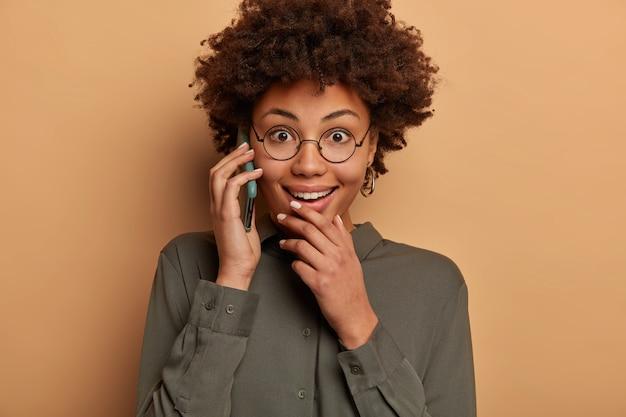 Zadowolona, zaskoczona afroamerykanka radośnie rozmawia przez smartfona, cieszy się reakcją na niesamowite wieści, omawia nieoczekiwane plotki, lubi miłą rozmowę