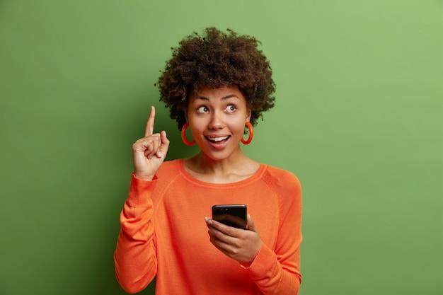 Zadowolona, zaskoczona kobieta z krągłymi włosami afro skierowanymi w górę z palcem wskazującym używa smartfona, który sugeruje sprawdzenie informacji, nosi swobodny pomarańczowy sweter odizolowany na zielonej ścianie