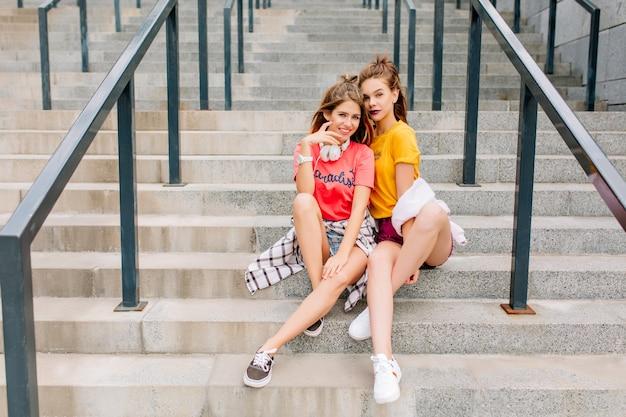 Zadowolone koleżanki schładzają się razem na kamiennych schodach ze skrzyżowanymi nogami, pozując emocjonalnie