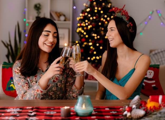 Zadowolone ładne młode dziewczyny brzęczą kieliszkami szampana, siedząc przy stole i ciesząc się świętami w domu