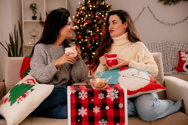 Zadowolone, ładne młode dziewczyny trzymają filiżanki i patrzą na siebie siedząc na fotelach i ciesząc się świątecznymi chwilami w domu