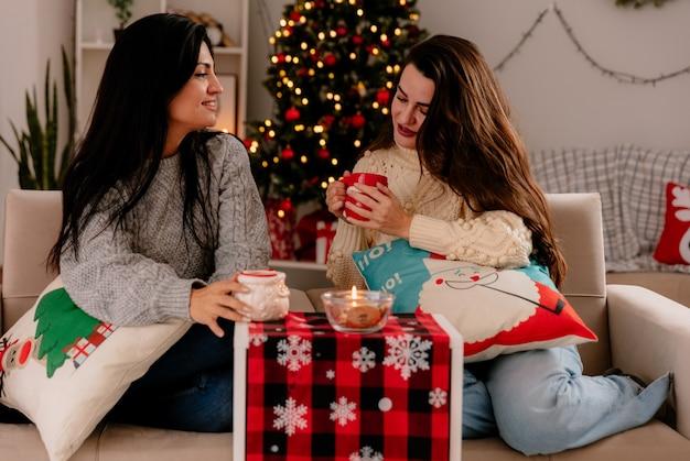 Zadowolone, ładne młode dziewczyny trzymają i patrzą na kubki siedząc na fotelach i ciesząc się świątecznymi chwilami w domu