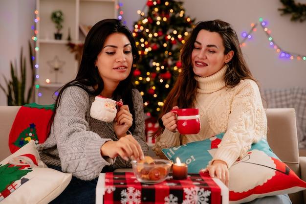Zadowolone ładne młode dziewczyny trzymają kubki i patrzą na herbatniki siedzące na fotelach i cieszące się świętami bożego narodzenia w domu