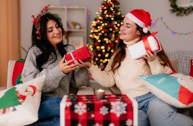 Zadowolone ładne młode dziewczyny w czapce mikołaja i wieńcu ostrokrzewu trzymają i patrzą na pudełka z prezentami siedząc na fotelach i ciesząc się świątecznymi chwilami w domu