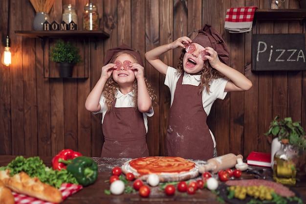Zadowolone małe siostry w fartuchach i czapkach trzymające kiełbaski w pobliżu oczu podczas wspólnego przygotowywania pizzy w kuchni