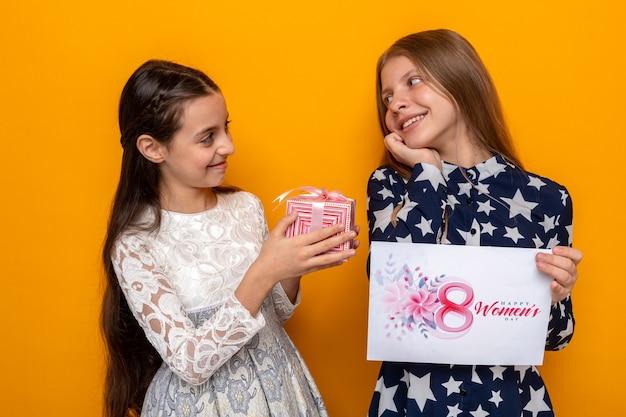Zadowolone patrząc na siebie dwie małe dziewczynki na szczęśliwy dzień kobiet trzymające prezent z kartką z życzeniami