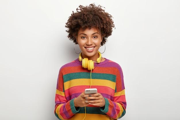Zadowolony african american nastoletnia dziewczyna trzyma telefon komórkowy podłączony do słuchawek