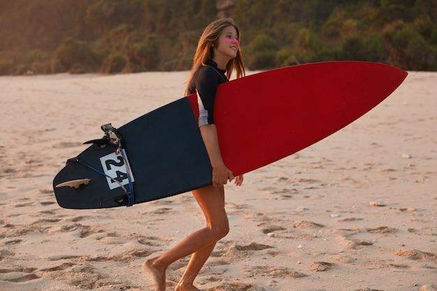 Zadowolony aktywny surfer niesie ze sobą deskę surfingową