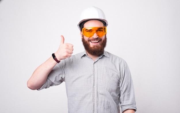 Zadowolony architekt brodaty w kasku i okularach ochronnych pokazuje kciuk w stronę kamery w pobliżu białej ściany