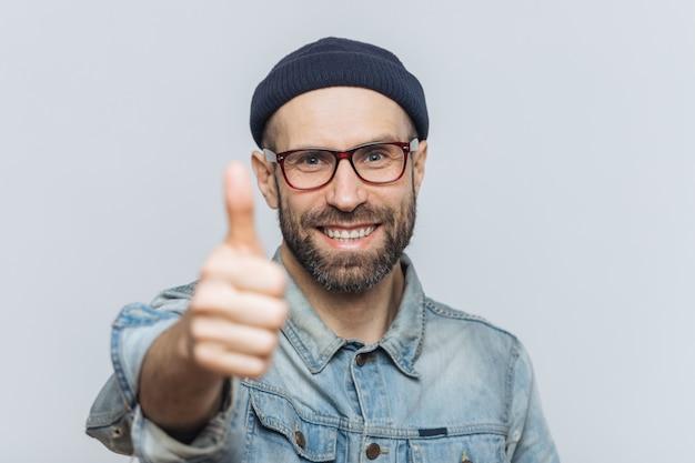 Zadowolony atrakcyjny brodaty mężczyzna o radosnym wyrazie, nosi modny kapelusz, dżinsową kurtkę i okulary