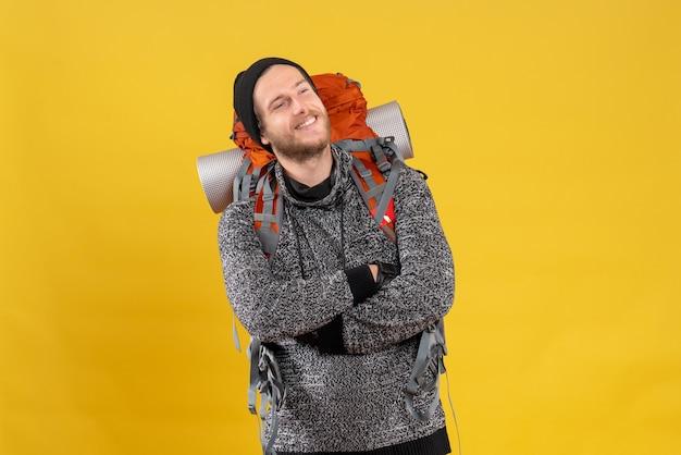 Zadowolony autostopowicz ze skórzanymi rękawiczkami i plecakiem krzyżującym ręce