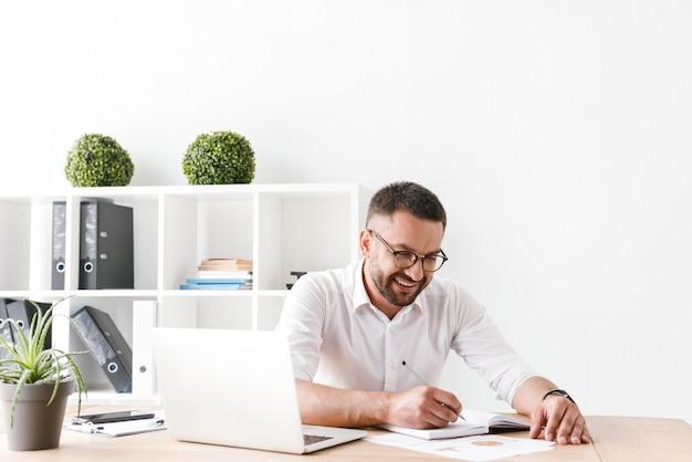 Zadowolony biznesmen 30s w białej koszuli siedzi przy stole i zapisując informacje w notebooku, podczas pracy z laptopem w biurze