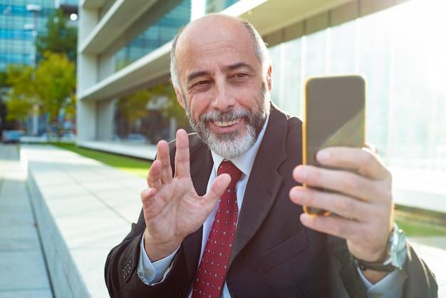 Zadowolony biznesmen macha ręką podczas czatu wideo
