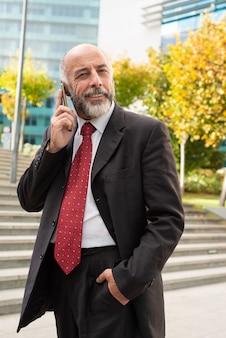 Zadowolony biznesmen opowiada smartphone i patrzeje