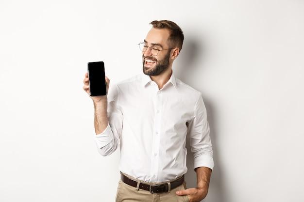 Zadowolony biznesmen pokazuje i patrzy na ekran telefonu komórkowego, wprowadza promo aplikacji lub strony internetowej, stojąc na białym tle.