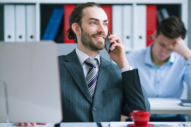 Zadowolony biznesmen rozmawia przez telefon w biurze