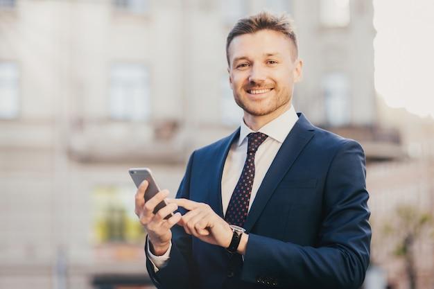Zadowolony biznesmen trzyma inteligentny telefon