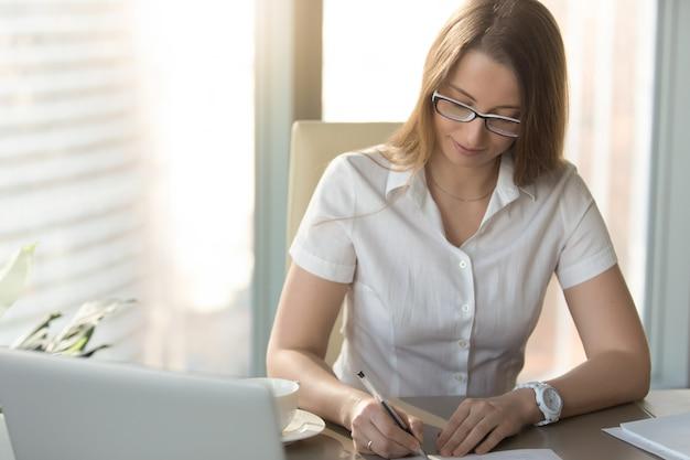 Zadowolony bizneswoman podpisuje kontrakt przy biurkiem