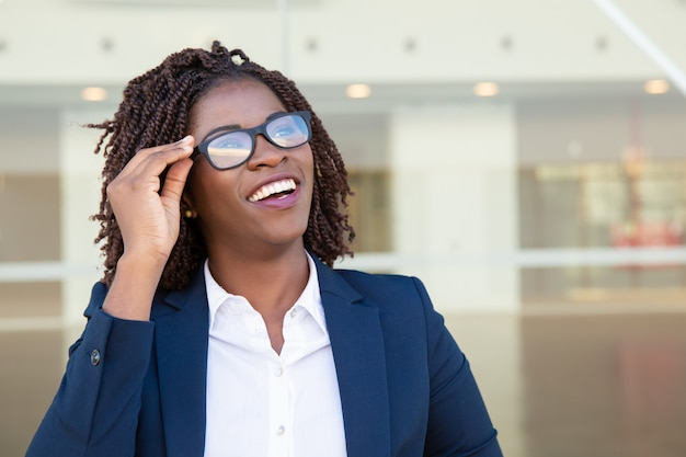 Zadowolony bizneswoman w eyeglasses przyglądający up