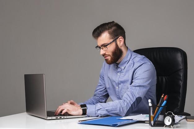 Zadowolony brodaty elegancki mężczyzna w okularach przy użyciu laptopa siedząc przy stole w biurze