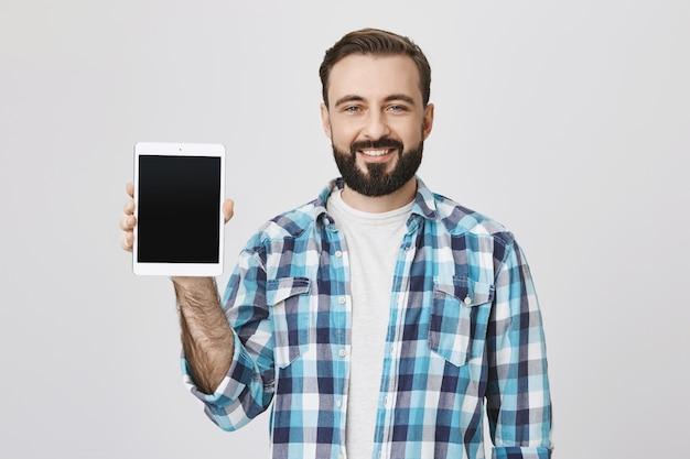 Zadowolony brodaty mężczyzna pokazuje ekran cyfrowego tabletu, uśmiechając się