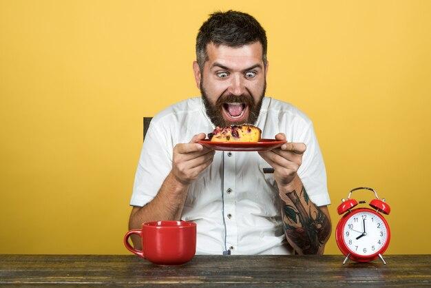 Zadowolony brodaty mężczyzna trzyma talerz z ciastem idealny poranek szczęśliwy przystojny mężczyzna siedzący przy stole