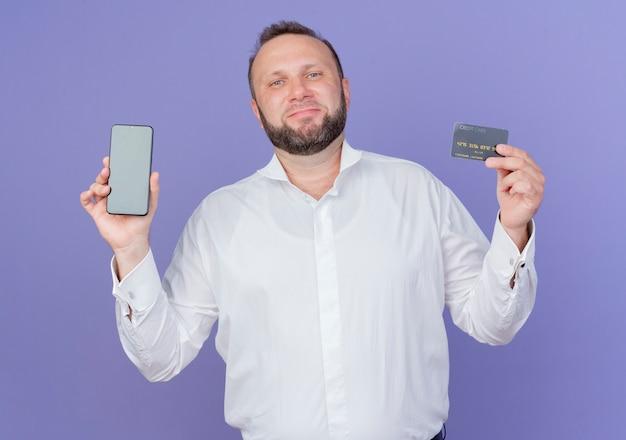 Zadowolony brodaty mężczyzna ubrany w białą koszulę pokazujący smartfon i uśmiechniętą kartę kredytową stojącą na niebieskiej ścianie