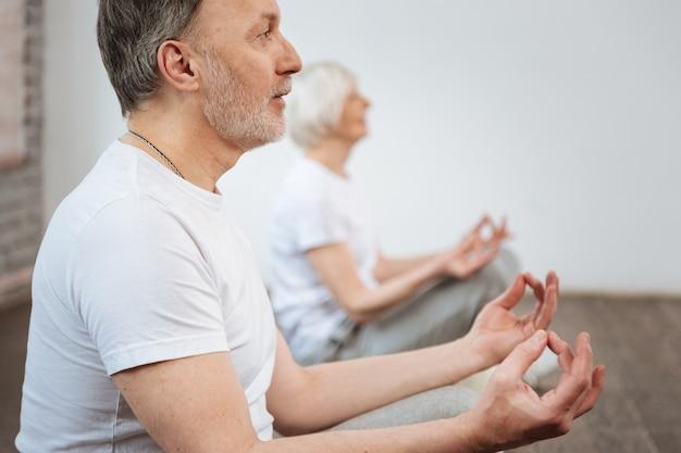 Zadowolony brodaty mężczyzna ubrany w białą koszulkę, ściskając kciuk i środkowy palec, siedzi obok żony