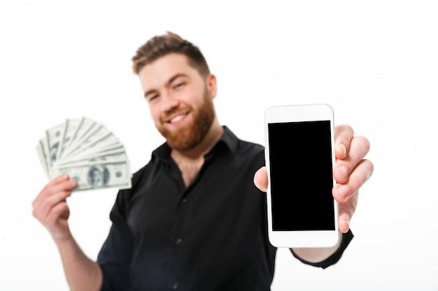 Zadowolony brodaty mężczyzna w koszuli gospodarstwa pieniądze
