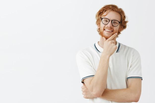 Zadowolony brodaty rudy facet pozuje przy białej ścianie w okularach